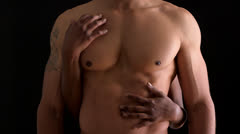 Shirtless black man being embraced by woman - stock footage