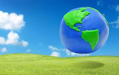 clay earth over the green grass field eco concept - stock photo