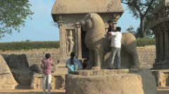 India Tamil Nadu Mahabalipuram Five Rathas boy sits on lion sculpture 10 Stock Footage