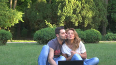 Smiling young couple using computer in park Stock Footage