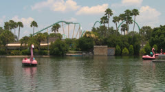 Lake with Paddle Boats and Rollercoaster in Background at Theme Park Stock Footage