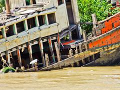 a wooden boat wreckage on the bank of chaopraya river in ayutthaya in thailan - stock photo