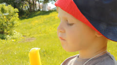 A little boy eating ice cream in a Panama hat on a background of nature Stock Footage