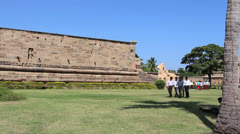 India Tamil Nadu Gangaikonda youth walking on lawn past wall 2 Stock Footage