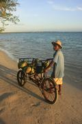 local man selling coconuts at boca chica beach - stock photo