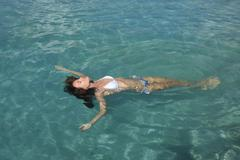 Young woman in bikini floating in clear water Stock Photos
