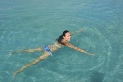 young woman in bikini swimming in clear water - stock photo