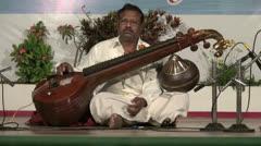 India Tamil Nadu seated musician plays maroon sitar Stock Footage