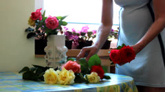 Women putting flowers in vase - stock footage