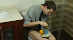 Funny man eating breakfast on the toilet Stock Footage