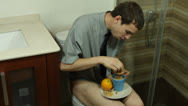 Stock Video Footage of Funny man eating breakfast on the toilet