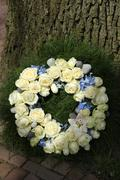 white roses on a sympathy wreasth - stock photo