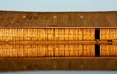 reflection of wood house in water - stock photo