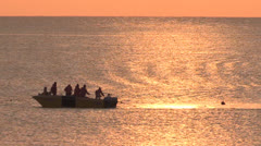 A small fishing boat at sea at sunrise Stock Footage