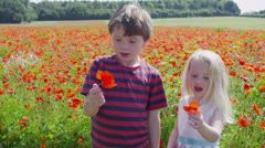 Cute and happy little boy and girl share a kiss in a meadow full of poppies Stock Footage
