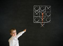 Pointing boy business man with thinking out of the box tic tac toe concept Stock Photos