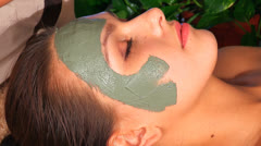 Woman with clay facial mask in spa. - stock footage