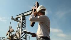 Man (engineer) with securities for the oil pumping unit Stock Footage