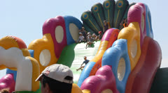 сhildren climb and slide on inflatable rubber castle playground Stock Footage