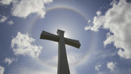 Stock Video Footage of Crucifix Cross with Halo Sun Flare Timelapse with White Clouds 1080p