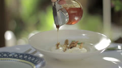 Pouring honey over yoghurt on a breakfast plate Stock Footage