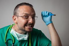 Funny crazy doctor holding a surgical knife Stock Photos
