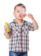 boy blowing soap bubbles on white - stock photo