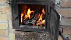 Firewood wood burn retro brick stove hand close rusty door Stock Footage