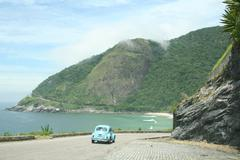 Volkswagon Bug | VW Beetle driving on mountain to the ocean - stock photo