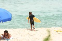 Surfer Kid Walks to the Ocean with Surfboard - stock photo