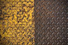 old metal diamond plate with yellow paint on surface - stock photo