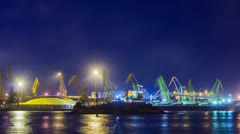 Timelapse of unloading sulfur in trading seaport at night Stock Footage