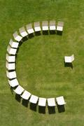 Chairs arranged in a half circle on a sunny meadow Stock Photos