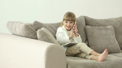 Young businesswoman  sitting on couch with tablet and talking on phone - stock footage