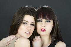 two beautiful young sensual glamour women standing together over white backgr - stock photo