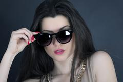 Beautiful long hair brunette woman wearing sunglasses portrait, studio shot Stock Photos