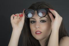 beautiful long hair brunette woman wearing sunglasses portrait, studio shot - stock photo