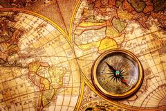 vintage compass lies on an ancient world map. - stock illustration