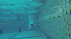 A slow motion ramp effect of someone diving into a swimming pool Stock Footage