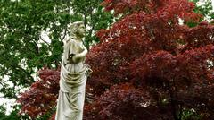 Statue Praying by Red Maple - stock photo