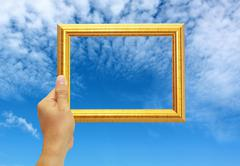 A hand is holding a gold photoframe against the blue sky Stock Photos