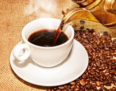 hot coffee from arabic copper turks and  scattered coffee grains - stock photo