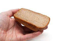 piece of the pumpernickel in hand - stock photo