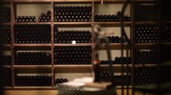 Wine bottles on a shelf - dolly shot - stock footage