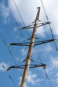 Pole high-tension wire on background blue sky Stock Photos