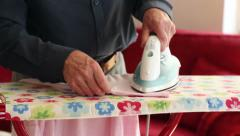 Left handed senior man ironing clothes Stock Footage