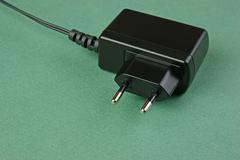 black charger adapter with plug on the green background - stock photo