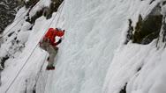 Ice climber frozen waterfall Stock Footage