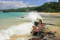Young woman in bikini sitting on rocks at rincon beach, samana peninsula Stock Photos
