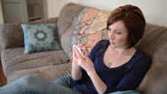 Stock Video Footage of Woman sits on couch and types on her smart phone